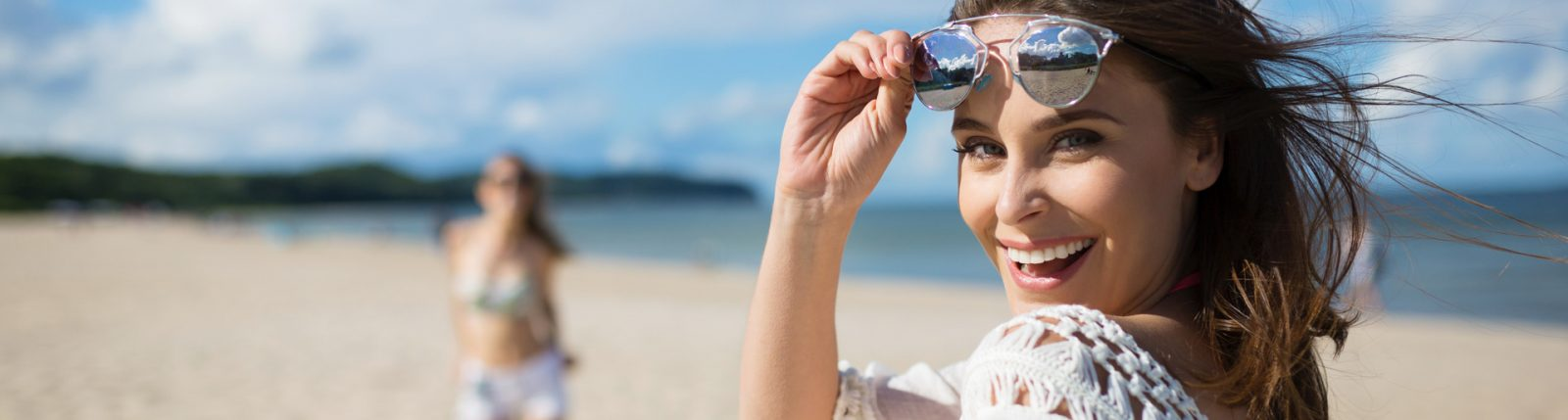 stock image of model smiling on beach, close up of teeth