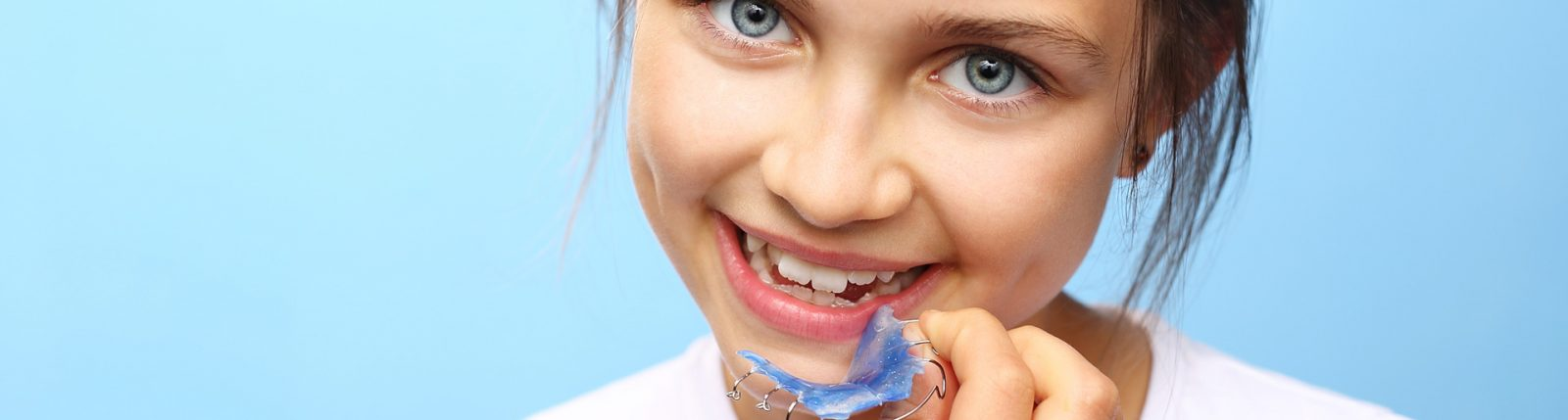 photo of child holding plate in front of teeth