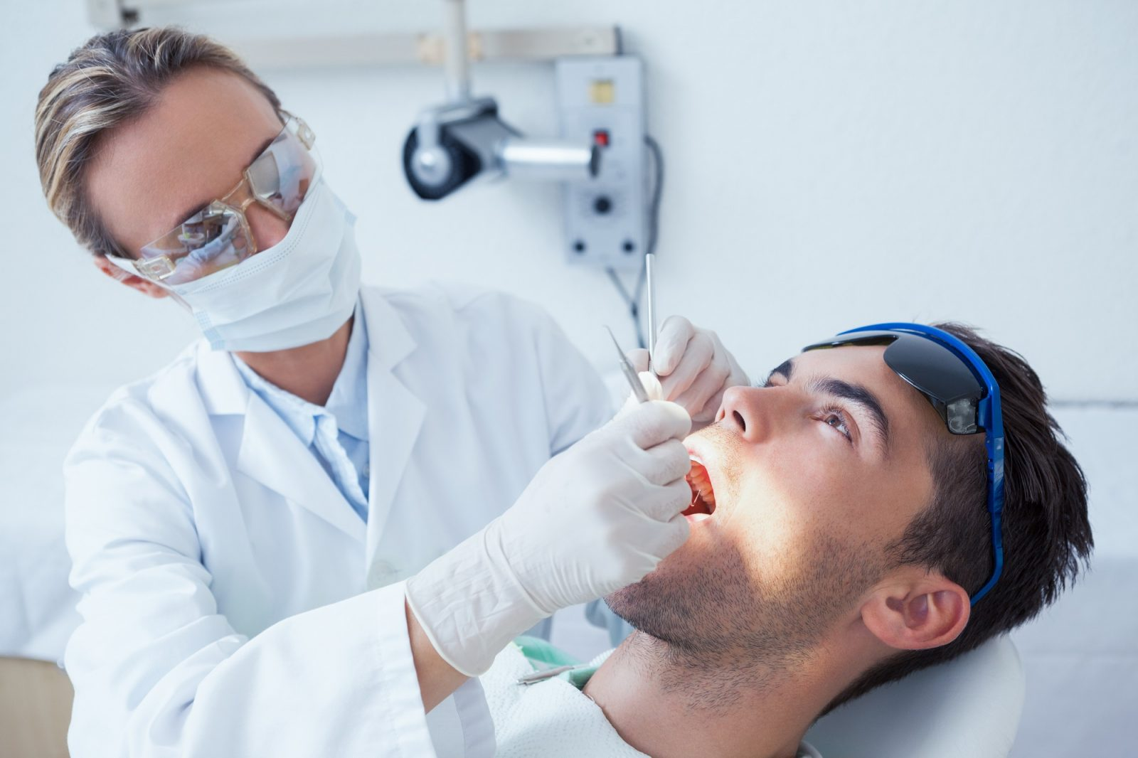 image of man in dentist chair having tooth extracted